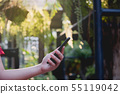 Smart phone on hand woman in the park, used mobile 55119042