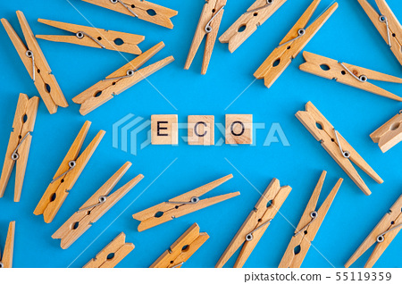 Wooden clothespins are scattered on a white and 55119359