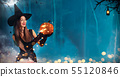 Beautiful young woman holding carved pumpkin 55120846