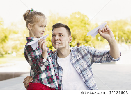 Charming daughter launching paper planes with father 55121608