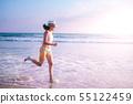 young woman on sunset beach and joyful running . 55122459