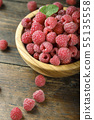 Fresh raspberries in a wooden bowl on a wooden 55135558