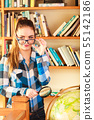Girl in library with globe and magnifying glass 55142186