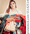 Young woman hold pile of clothes. 55142514