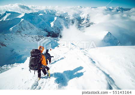 A group of climbers ascending a mountain in winter 55143164