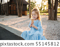 Beautiful little girl in a blue dress eating an ice cream 55145812