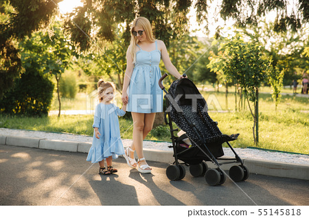 Little daughter helps mom push the baby carriage 55145818