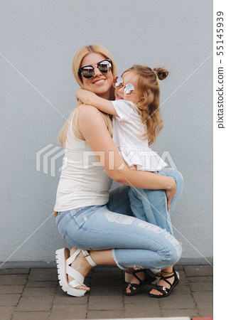 Beautiful mothe with her daughter. Blond hair female. Gray background. Best friends 55145939