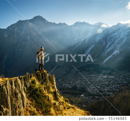 Backpacker sit on cliff edge and looks at mount 55146985