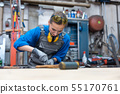 Woman metalworker marking piece of steel 55170761