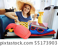 tourist woman with beach straw hat packing suitcase for beach 55173903