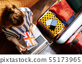 woman with Great Britain flag diary while booking hotel online 55173965