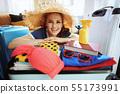 woman with big beach straw hat preparing for summer trip 55173991