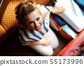 smiling young woman packing stuff in open travel suitcase 55173996