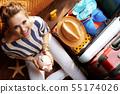 smiling elegant woman holding piggy bank 55174026
