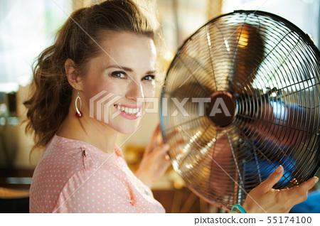 happy stylish housewife enjoying freshness in front of fan 55174100