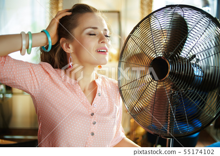 relaxed young woman enjoying fresh air in front of working fan 55174102
