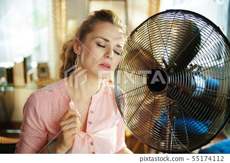 woman enjoying breeze near fan suffering from summer heat 55174112
