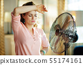 woman exhausted from summer heat while standing in front of fan 55174161