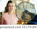 smiling elegant housewife near metallic floor standing fan 55174184