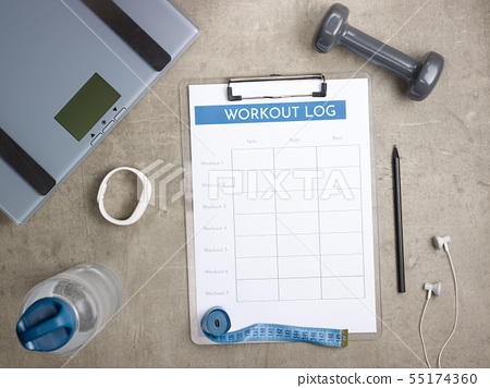 weight scales, black pen and workout log on clipboard 55174360