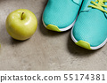 Closeup on green apple and sneakers on floor 55174381