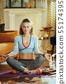 relaxed fit sports woman in modern house meditating 55174395
