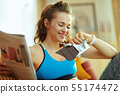happy active sports woman reading magazine and eating chocolate 55174472