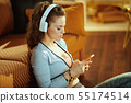 woman in white headphones sending text message from phone 55174514