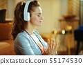 relaxed fit sports woman in white headphones meditating 55174530