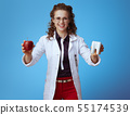 medical practitioner woman showing red apple and white tooth 55174539