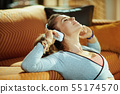 sports woman listening to music with headphones in modern house 55174570