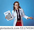 medical doctor woman with big white calculator shrug on blue 55174594