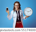 happy doctor woman showing smartphone and round clock on blue 55174600