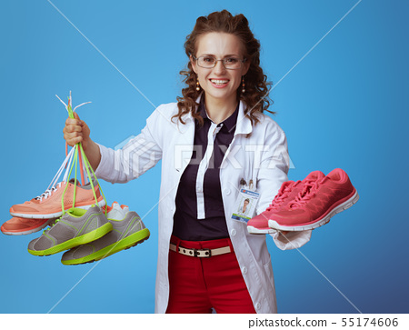 physician woman giving one pair of fitness sneakers while holdin 55174606