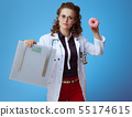medical practitioner woman showing weight scale and donut 55174615