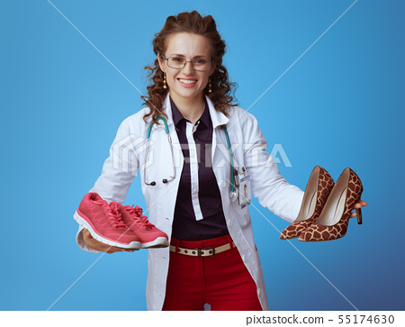 medical doctor woman showing sneakers and high heel shoes 55174630