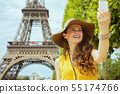 smiling trendy traveller woman taking selfie with smartphone 55174766