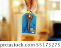 Closeup on door keys with label in hand of modern woman 55175275
