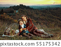 mother and child hikers embracing while sitting on blanket 55175342