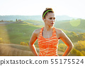 active woman jogger in Tuscany, Italy looking into distance 55175524