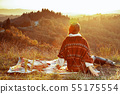 solo tourist woman in Tuscany on sunset sitting on blanket 55175554