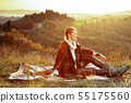 smiling active woman in Tuscany on sunset sitting on blanket 55175560