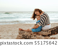 mother and daughter tourists hugging while sitting on a wooden s 55175642