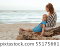mother and child sitting on wooden snag on beach in evening 55175661
