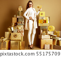 smiling stylish woman holding golden gift card with bow 55175709