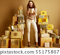 smiling woman among 2 piles of golden gifst holding diary 55175807