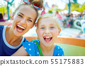 smiling mother and child tourists in theme park having ride 55175883