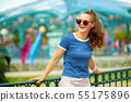 smiling trendy woman in theme park looking into distance 55175896