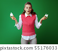 learner woman with 2 pieces of puzzle isolated on green 55176033
